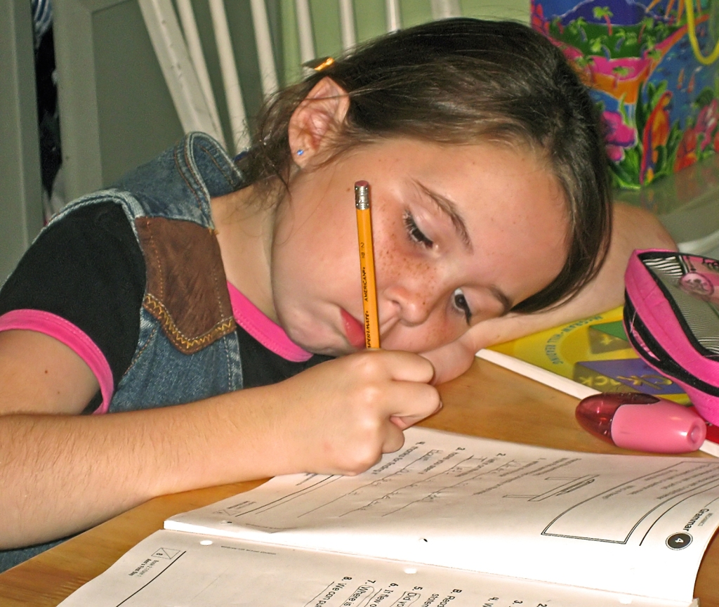 Girl at home writing in a homework book.