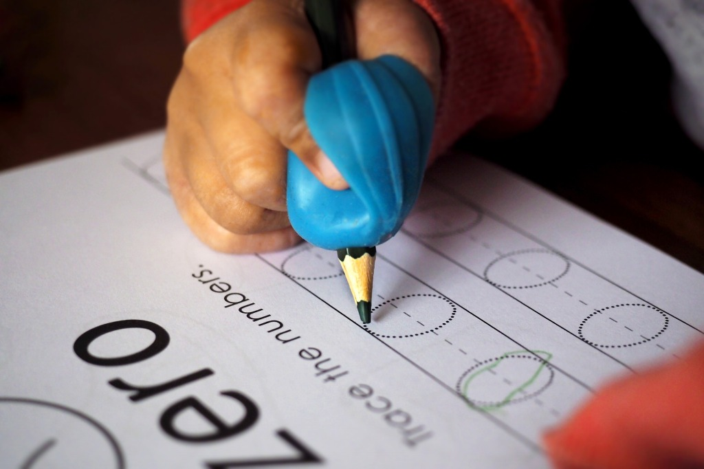 Student with dyspraxia writing with a pencil grip.